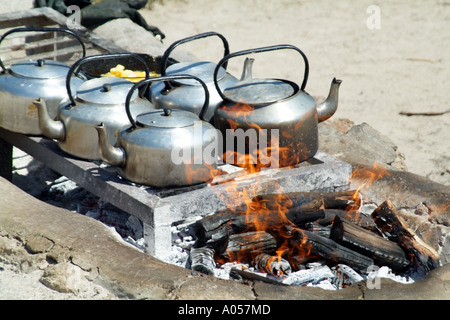 Kettles on the boil over open wood flaming fire Beach restaurant Langebaan western cape South Africa RSA - Stock Photo