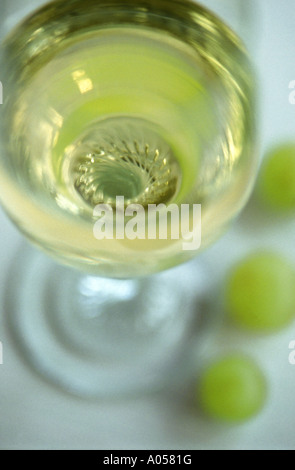 Abstract shot looking into a glass of white wine with three grapes at the base - Stock Photo