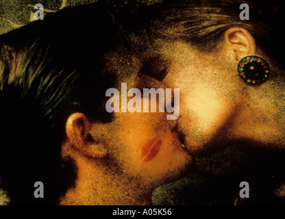Close up portrait of a couple engaged in a passionate kiss with an imprint of lipstick on the man cheek - Stock Photo