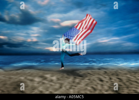 Woman running along the beach flying a flag of the U in the wind - Stock Photo
