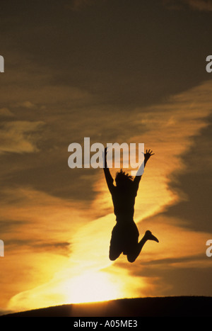 Silhouette of a woman jumping for joy with the sunset behind her - Stock Photo