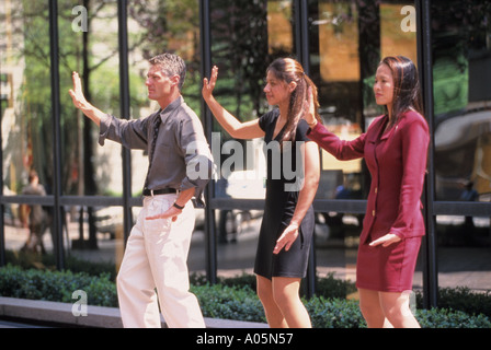A man and two women of different ethnicity practice Tai Chi martial arts outdoors while during their lunch break - Stock Photo