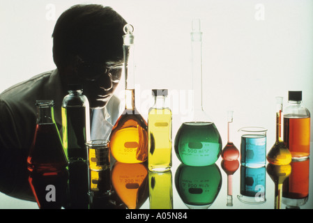 Male scientist over seeing a multitude of chemically filled beakers and flasks - Stock Photo