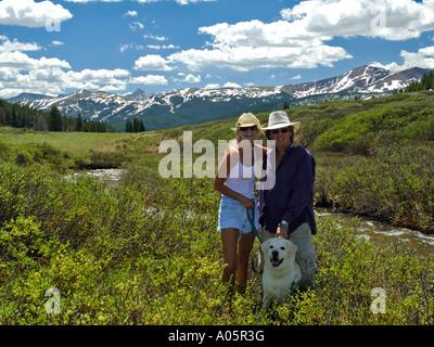 couple walking dog in meadow near Vail summit Colorado USA Rocky Mountains - Stock Photo