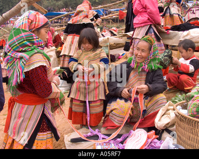 Vietnam Can Cau Flower H mong hilltribe market 3 generations of women wearing traditional scarf woven embroidered - Stock Photo