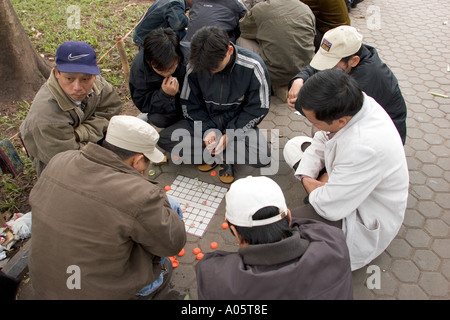 Vietnam Hanoi Old Quarter culture pastimes men playing game of Co Tuong Chinese Chess in public park - Stock Photo