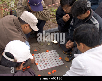 Vietnam Hanoi Centre Old Quarter culture pastimes men playing game of Co Tuong Chinese Chess in public park - Stock Photo