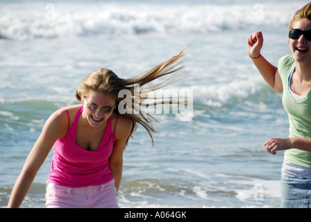 two teenage girls playing on beach together - Stock Photo