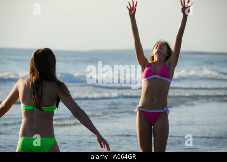 two teenage girls playing volleyball on the beach - Stock Photo