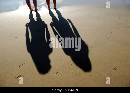 two teenage girls standing at edge of shore of ocean - Stock Photo
