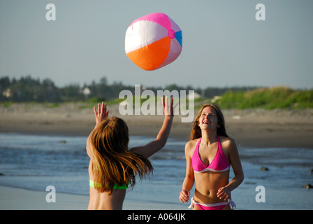 two teenage girls playing on beach with beach ball - Stock Photo