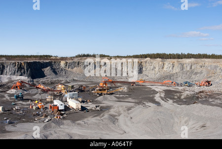 Machinery at the bottom of a rock quarry , Finland - Stock Photo