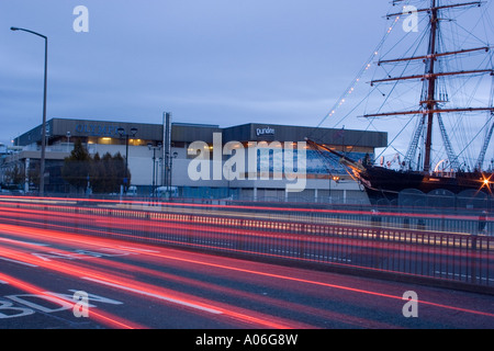 Streaks of vehicle light trails passing the RRS Discovery and Olympia Leisure club at night in Dundee, UK - Stock Photo