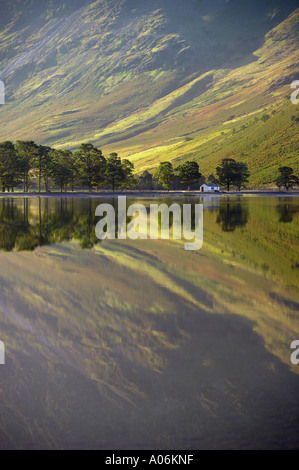 reflections on the shore of Buttermere at dawn Lakes District Cumbria England UK - Stock Photo