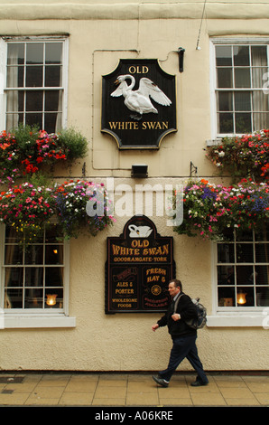 Man walking past the front of the Old White Swan public house in Goodramgate, York - Stock Photo