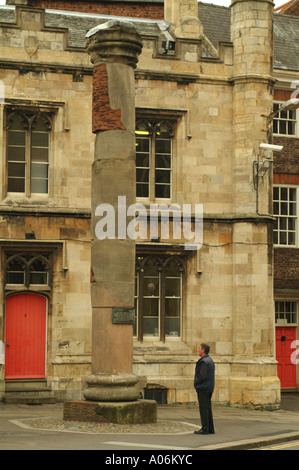 Man reading the plaque on the Roman Column in Minster Yard, York - Stock Photo
