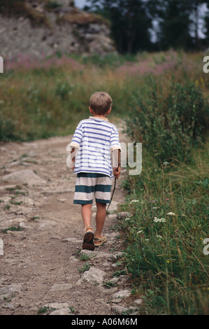 Six Year Old Boy walks down rocky path Czech Republic - Stock Photo