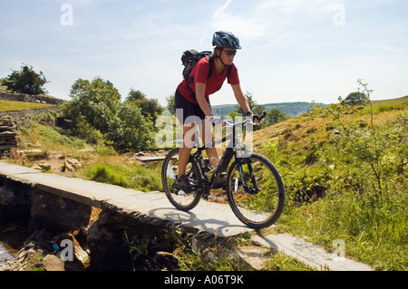 Female mountain biker on ancient stone bridge between Clapham and Austwick in the Yorkshire Dales - Stock Photo