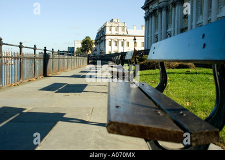 row of benches outside Trinity College, Greenwich University, overlooking the River Thames in London - Stock Photo