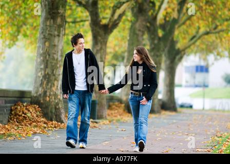 teenage couple walking hand in hand - Stock Photo