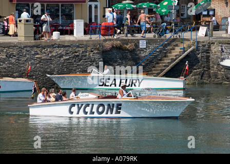 Speedboat departing quayside at Padstow harbour Cornwall England UK with passengers on board on a hot summers day - Stock Photo