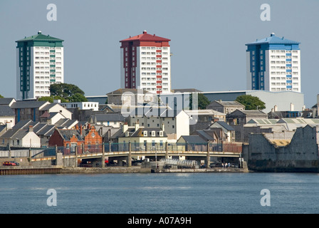 Plymouth three high rise blocks of waterside flats painted in different bold colours rising above houses & industrial - Stock Photo