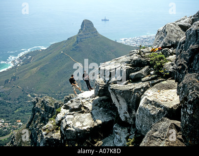 CAPE TOWN SOUTH AFRICA October Abseiling from the top of Table Mountain with the Lion's Head in the background - Stock Photo