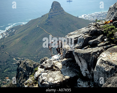 CAPE TOWN SOUTH AFRICA October Abseiling from the top of Table Mountain with the Lions Head in the background - Stock Photo