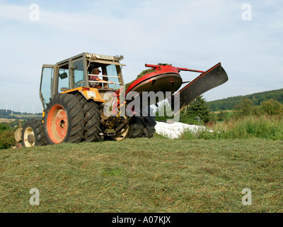 producing silage compressing the gras hay with a tractor in a field silo - Stock Photo