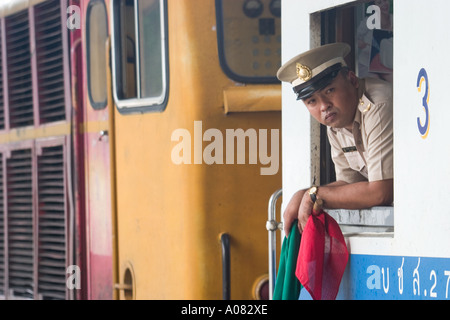 Thailand Train conductor leans out window at Thonburi station with flags in hand - Stock Photo