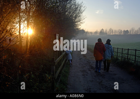 Family and friends walking down a country track at Thorncombe Woods in England UK - Stock Photo