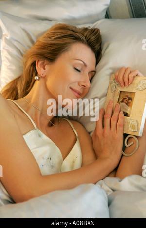 Frau liegt mit Foto im Bett und denkt an ihren Liebsten, woman lying in bed and thinking of her sweetheart - Stock Photo