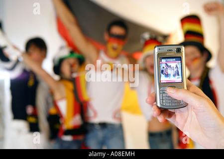 Gruppe deutscher Fussball Fans, woman make picture with mobile phone from a group of German football fans - Stock Photo