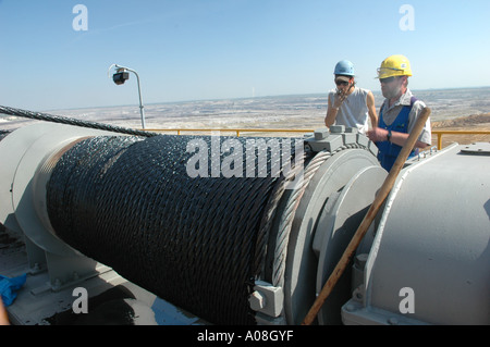 two workers standing on a dragline taliking to each other - Stock Photo
