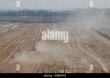 cars driving in the dirt in a strip mine with huge dust clouds behind them and wind turbines in the background - Stock Photo