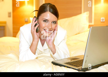 businesswoman laying on bed in hotel room stock photo royalty free image 72130773 alamy. Black Bedroom Furniture Sets. Home Design Ideas