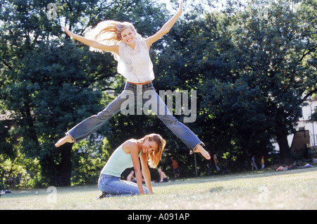 A woman jumping over another crouching on the ground - Stock Photo