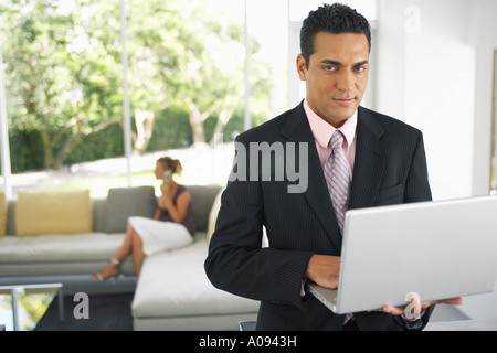 Businessman Holding Laptop, Woman in Background - Stock Photo