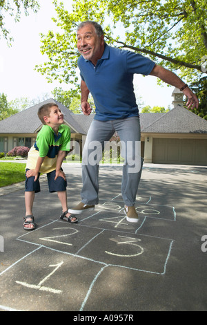 Grandfather and Grandson Playing Hopscotch - Stock Photo