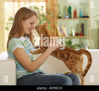 girl with domestic cat on a sofa - Stock Photo