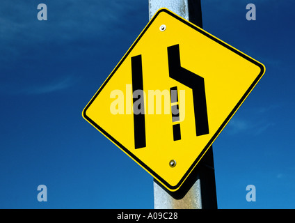 A yellow and black diamond shaped merge left road sign on a thick concrete post against a background of a clear - Stock Photo