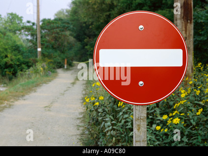A red and white circular no entry road sign on a wooden post situated beside a dirt road that becomes a dead end - Stock Photo
