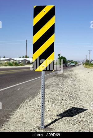Yellow and black diagonally striped rectangular hazard beside road sign - Stock Photo