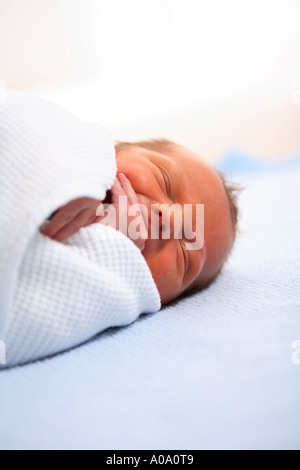Newborn baby sleeping in blanket - Stock Photo