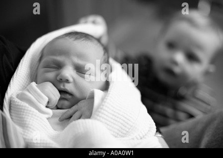 Newborn baby with 18 month old brother in background. - Stock Photo