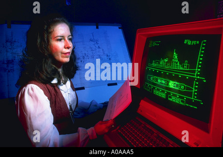 Woman works on design of ship with computer model released - Stock Photo