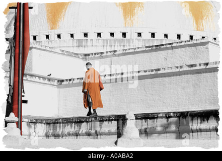 A Buddhist monk walks around Boudhanath Stupa - Stock Photo