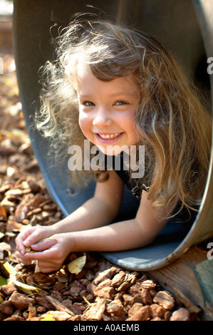 A cute little girl in a playground barrel. - Stock Photo