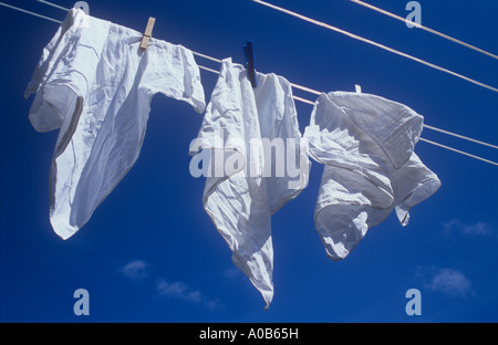 Close up of three white handkerchiefs blowing in the sun and breeze on washing-line under deep blue sky - Stock Photo