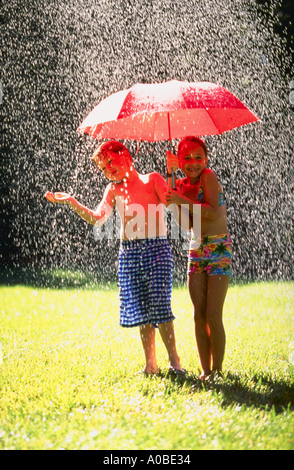 Boy and girl in swimsuits holding a red umbrella while standing under the shower of a sprinkler - Stock Photo